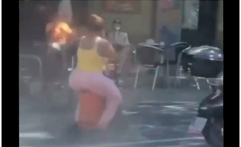 Mujer pasea en un scooter eléctrico sentada en un tanque de gas